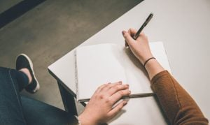 Girl putting pen to paper | Speech Planning In 5 Steps